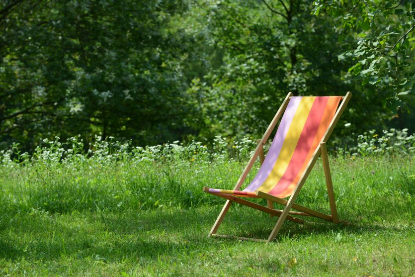 30660997 - wooden deckchair standing on the green in summer.