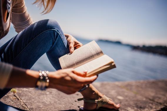 womenreadingbooknextto beach