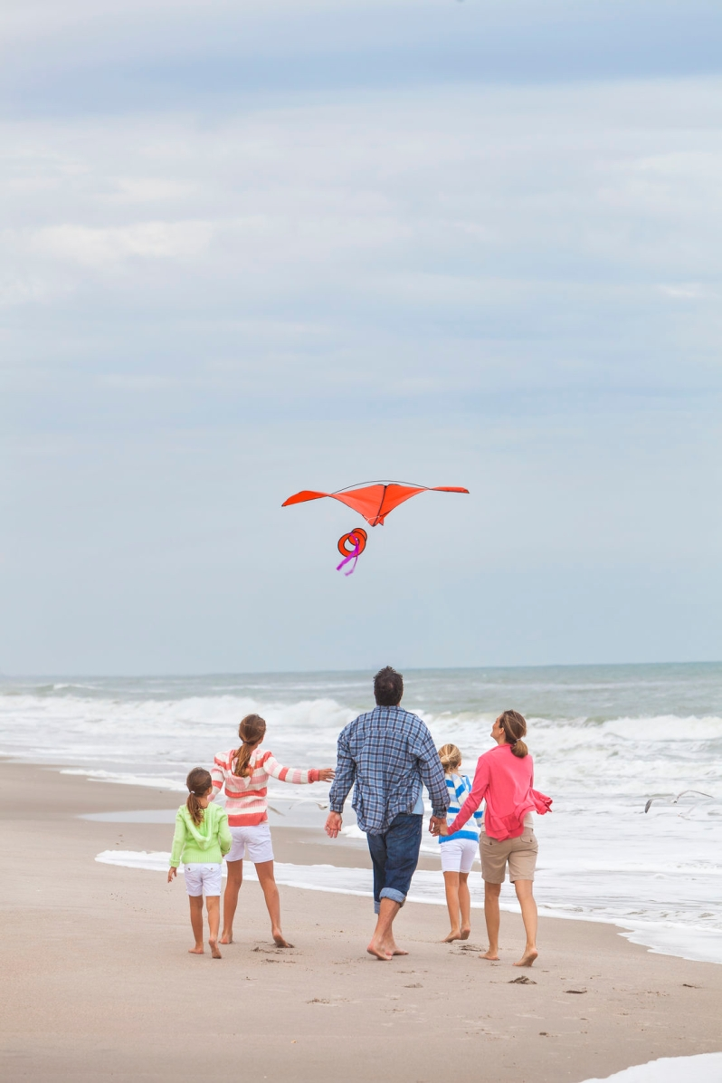 27696405 - happy family mother, father, daughter, parents and female girl children flying a red kite, playing & laughing on a beach